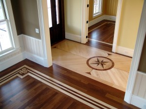 Combination of stained and natural flooring with an inlaid medallion and painted borders